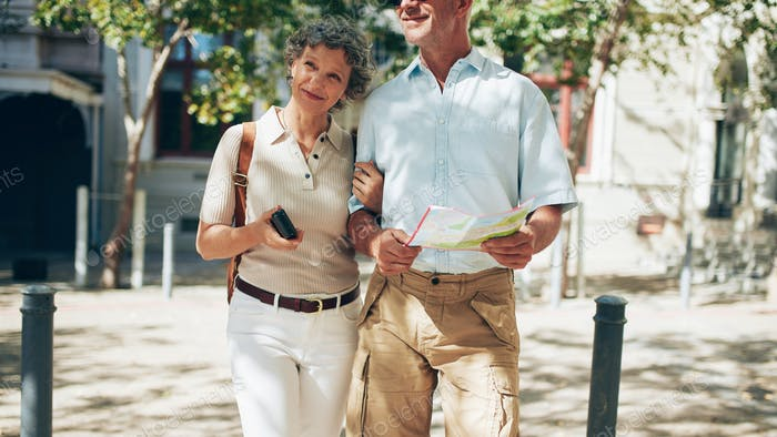 Senior couple walking around the city holding a map