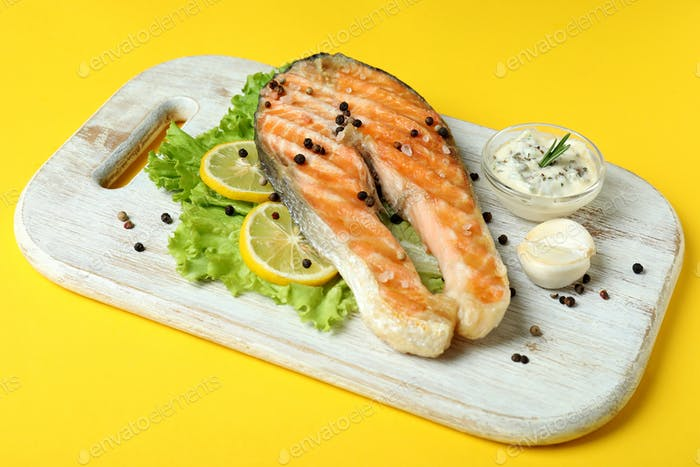 Concept of tasty eating with grilled salmon on yellow background