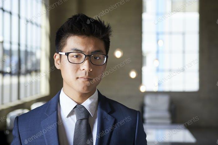 Junge asiatische Geschäftsmann auf der Suche nach Kamera, Kopf und Schultern