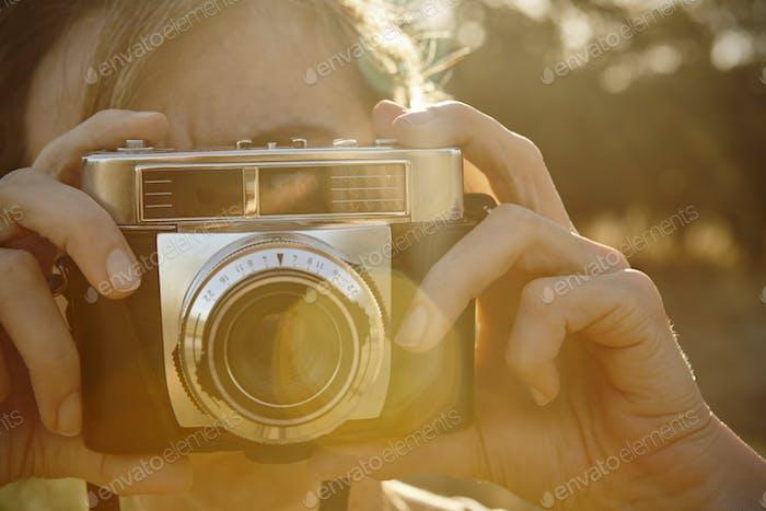 Frau fotografiert mit Vintage-Kamera. Reisehintergrund.