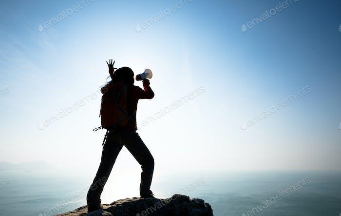 Woman shouting with loudspeaker on sunrise seaside