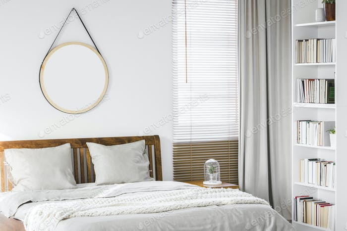 Fresh plant placed on bedside table next to king-size wooden bed