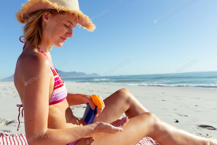 Woman applying sunscreen at the beach