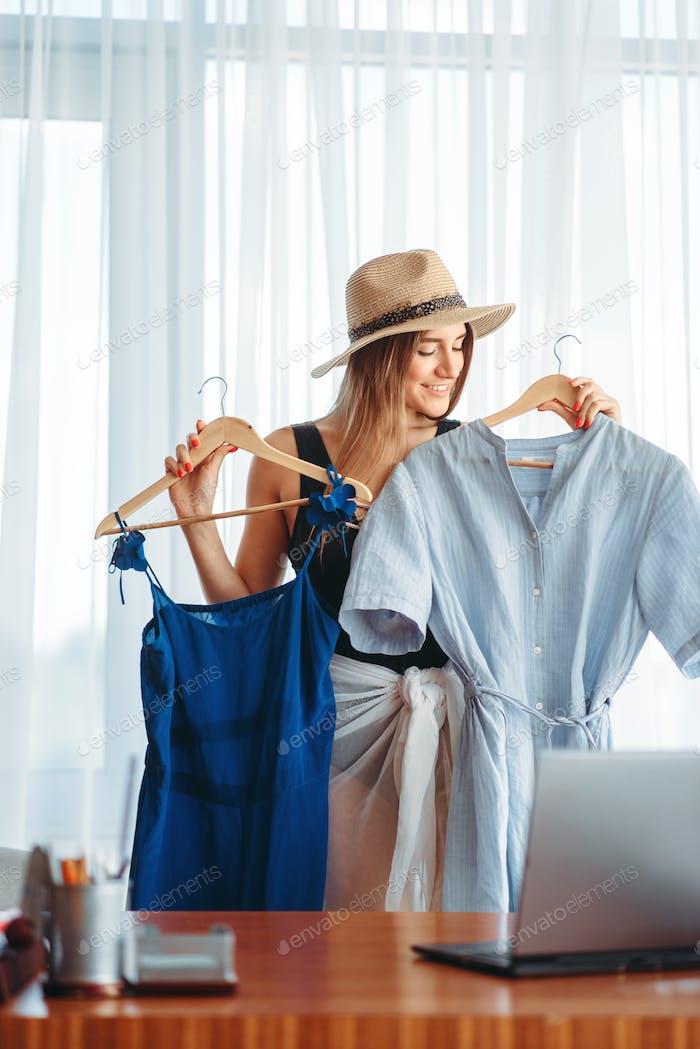 Frau wählt Kleider, träumt von einem Urlaub