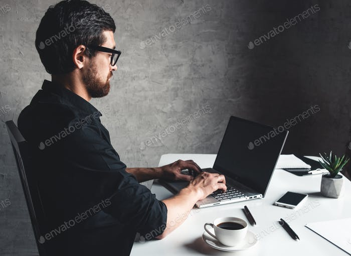 A man sits with a laptop in a black shirt. Business concept, work. Office routine. Property efforts