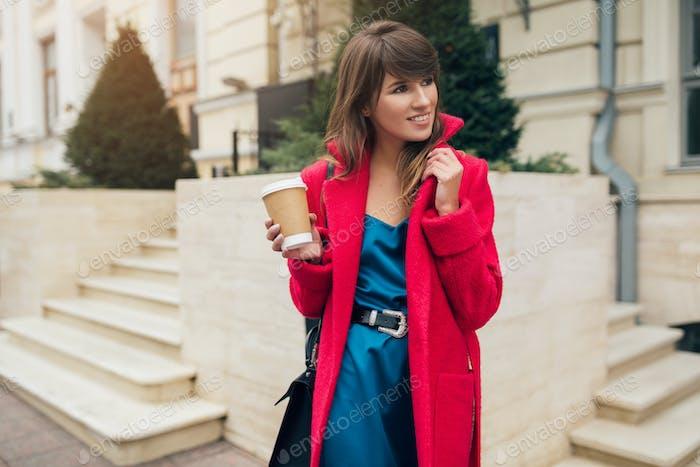 mujer con estilo en abrigo rojo caminando en la calle con el café