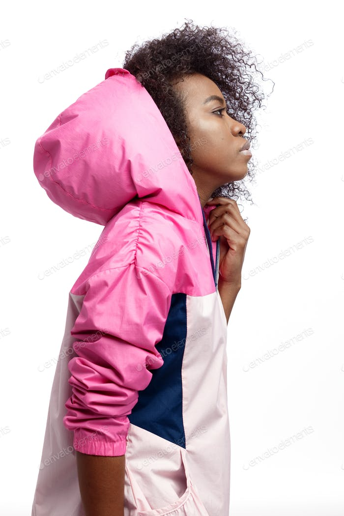 Mod young curly brown-haired girl dressed in the pink hooded sports jacket poses at the white