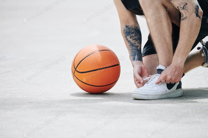 Basketball player tying sports shoe