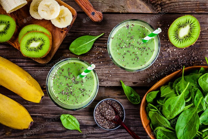healthy green smoothie with banana, kiwi, spinach and chia seeds in glass jars