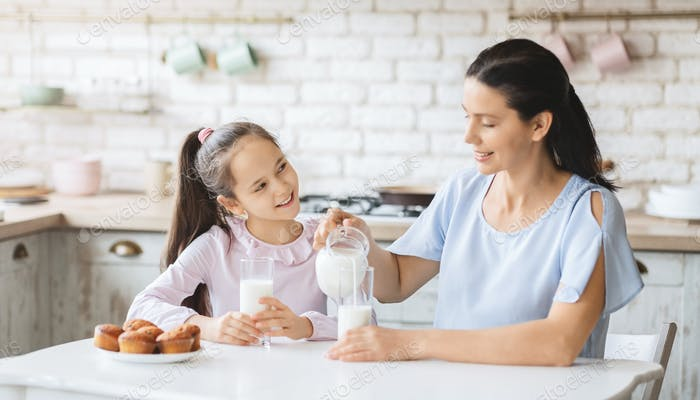 Beautiful mom and daughter drinking milk in kitchen together