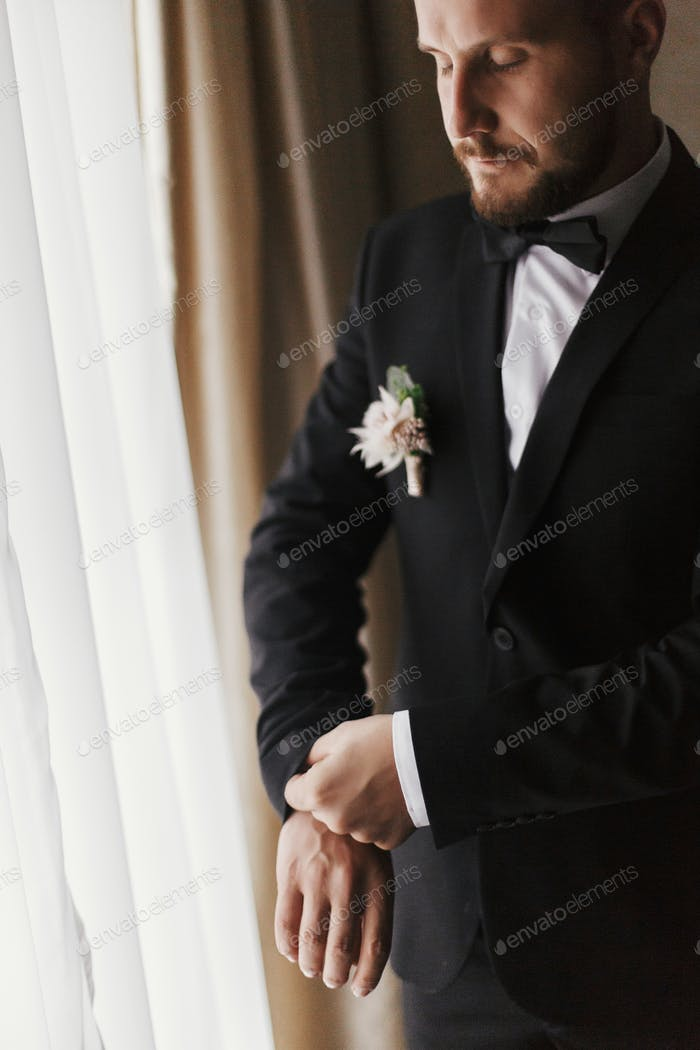 Stylish groom silhouette in suit posing at window light
