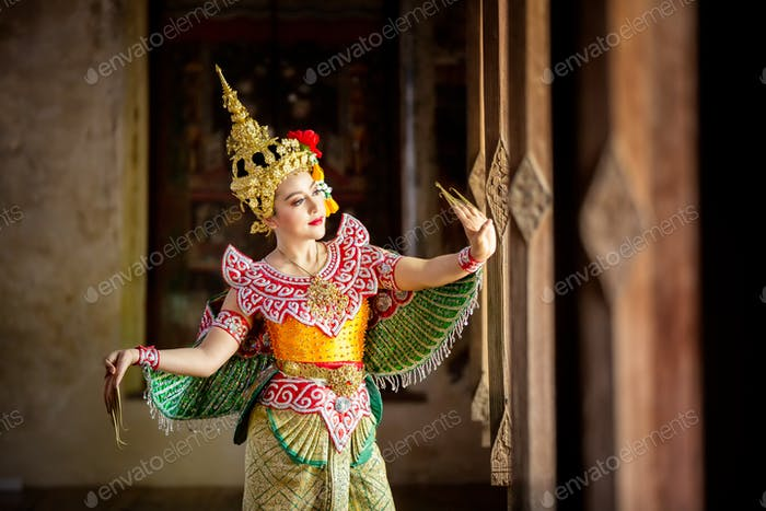Portrait of Thailand dancer in Kinnaree costume dancing against the temple wall