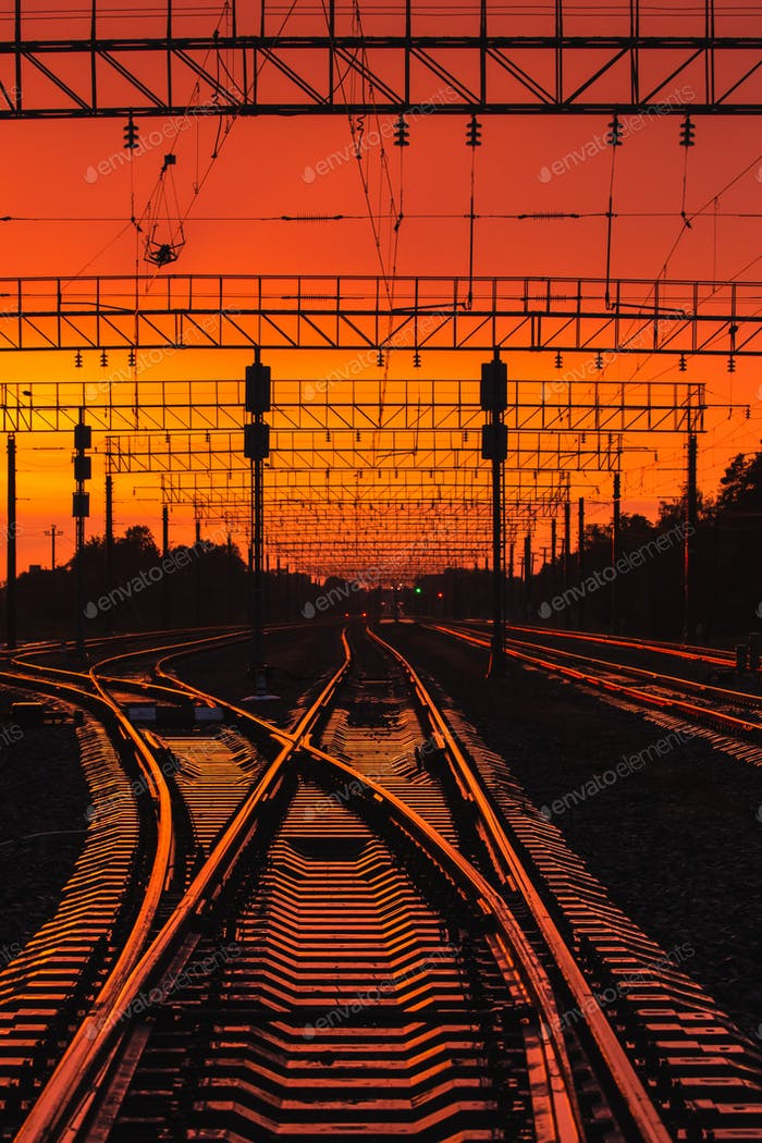 Dark Silhouettes Railway Infrastructure In Dramatic Sunset Backl