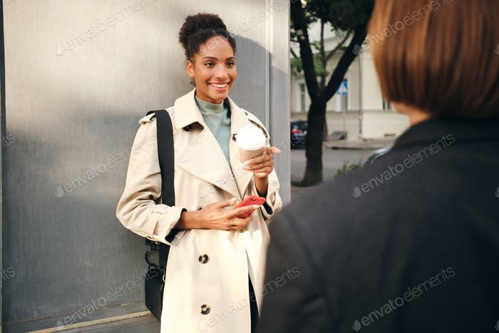 African American girl in stylish trench coat holding cellphone happily talking with friend outdoor
