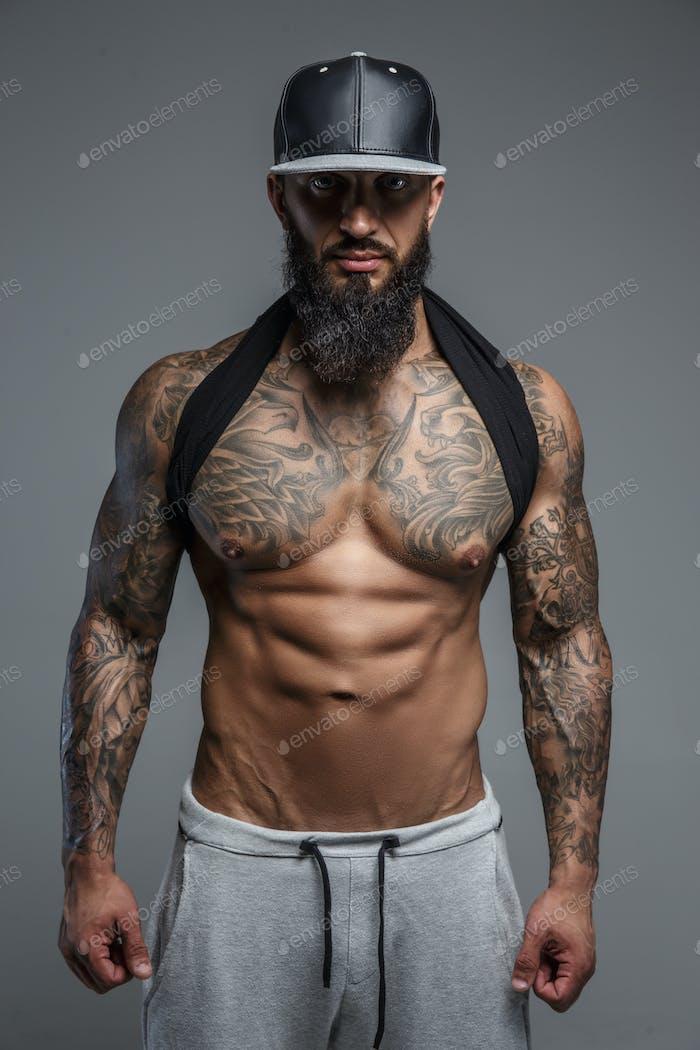 Shirtless tattooed man in black cap.