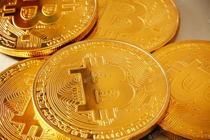 Shiny golden bitcoin on white background