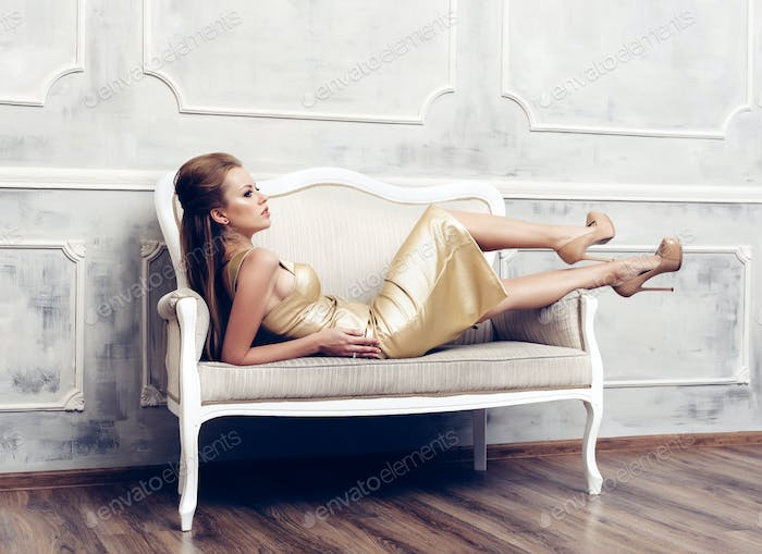 Young sexy beautiful woman in golden dress