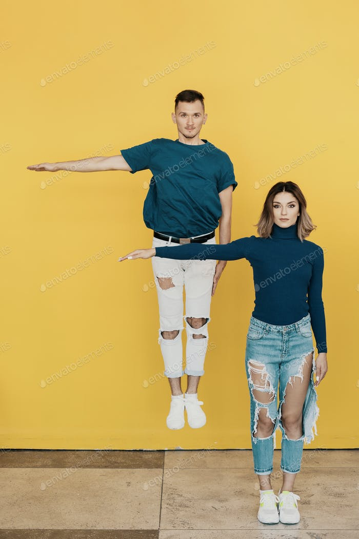 Colorful portrait of young man and woman on yellow background