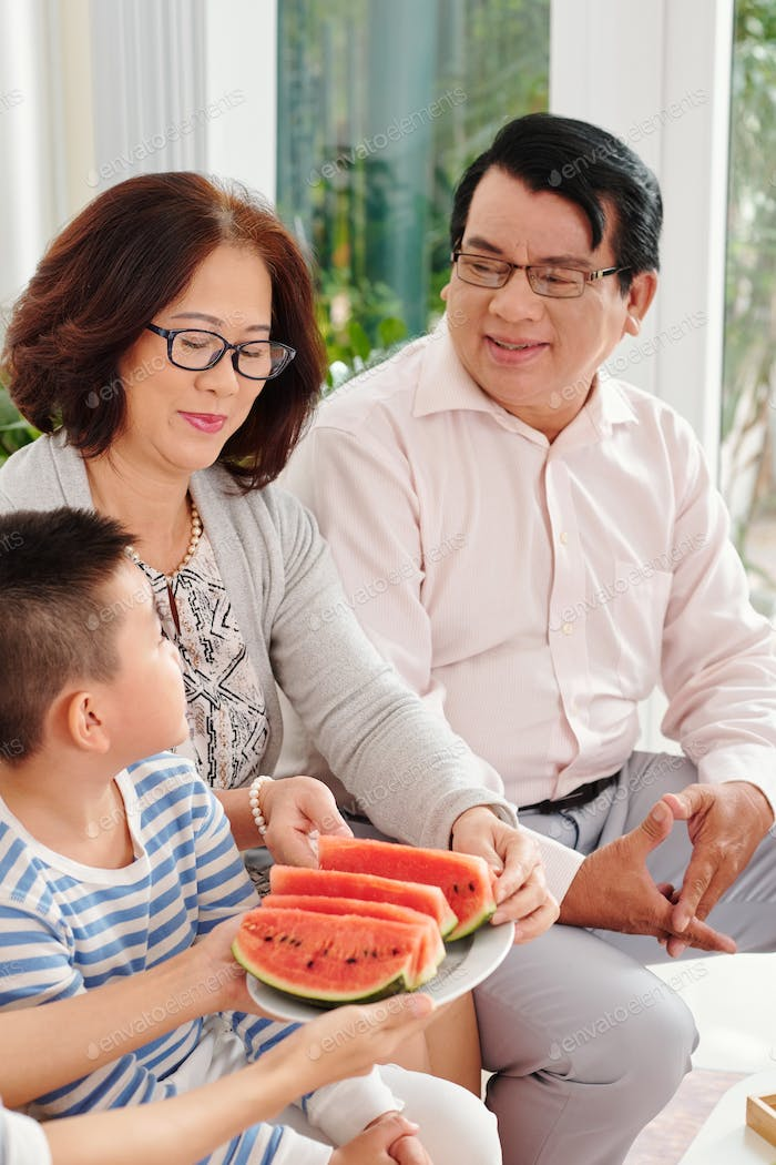 Offering watermelon slices to grandparents