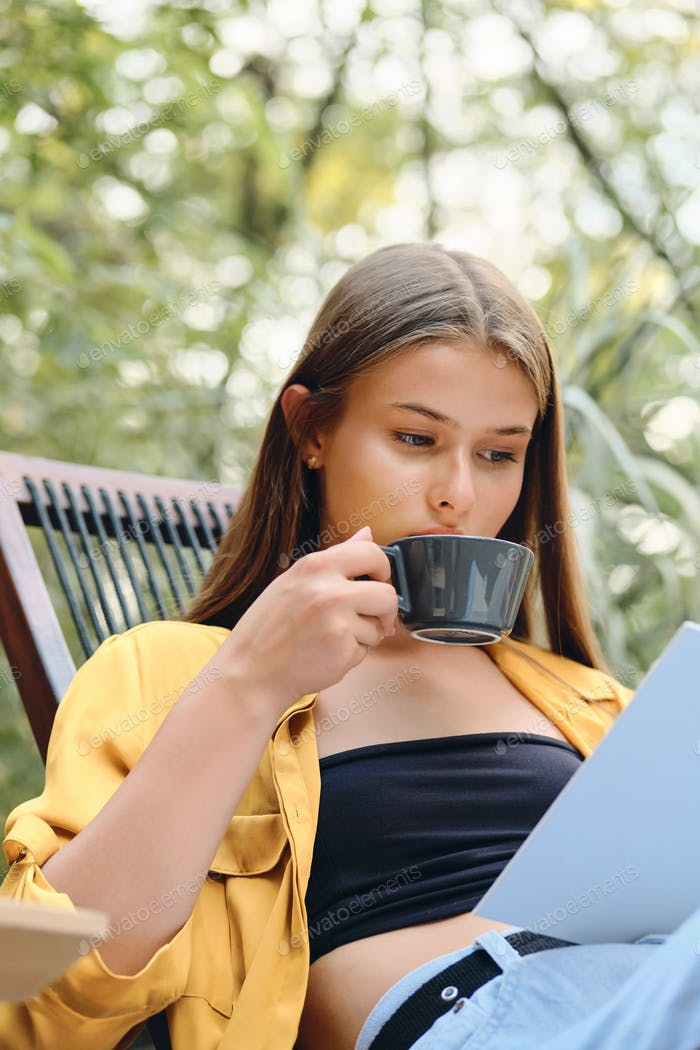 Young attractive thoughtful woman in yellow shirt reading book with coffee on wooden chair in park