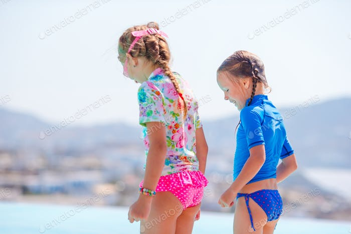 Adorable little girls on the edge of outdoor swimming pool with beautiful view