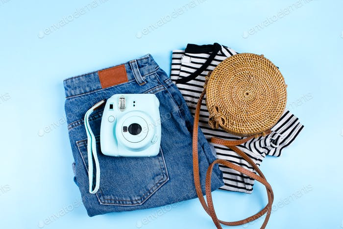 Blue jeans shorts, striped shirt, rattan bag on blue background. Summer outfit concept.