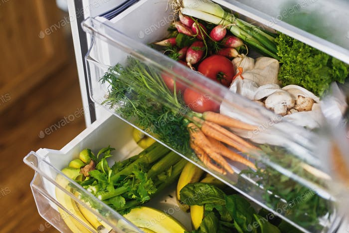 Zero waste grocery in fridge. Fresh vegetables in opened drawer in refrigerator.