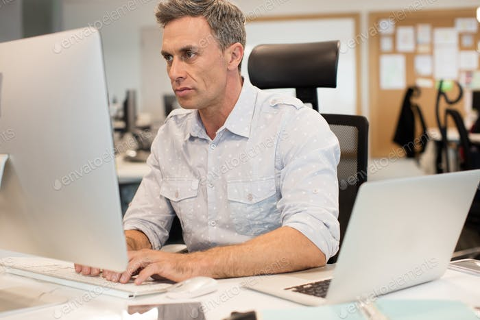 Serious businessman typing on computer in office