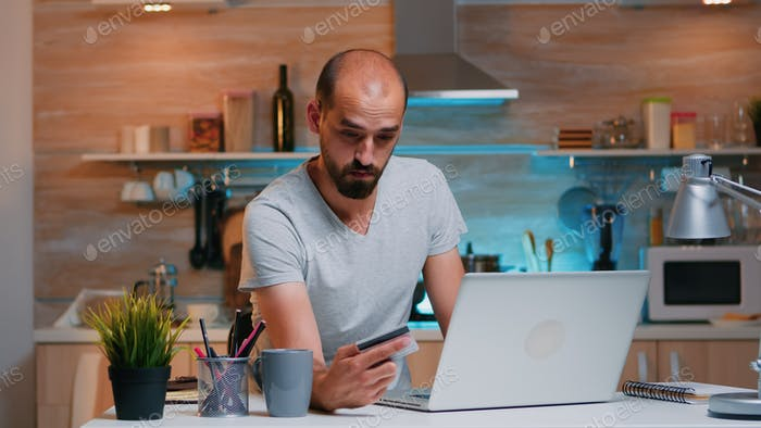Man shopping online late at night using credit card