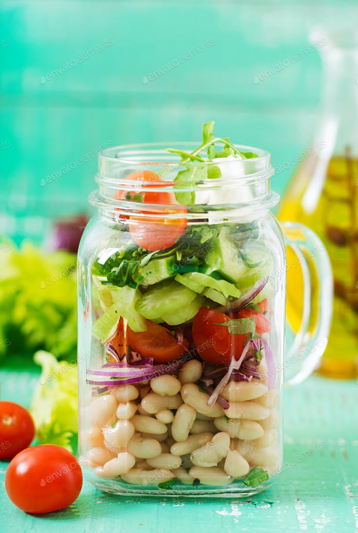 Ensalada de judías blancas, tomate, apio, pepino, rúcula, cebolla roja y queso feta en un frasco