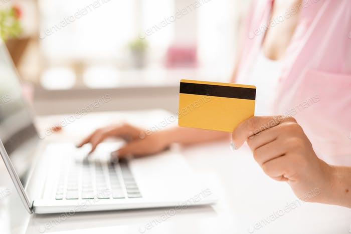 Plastic card in hand of young contemporary client of online shop