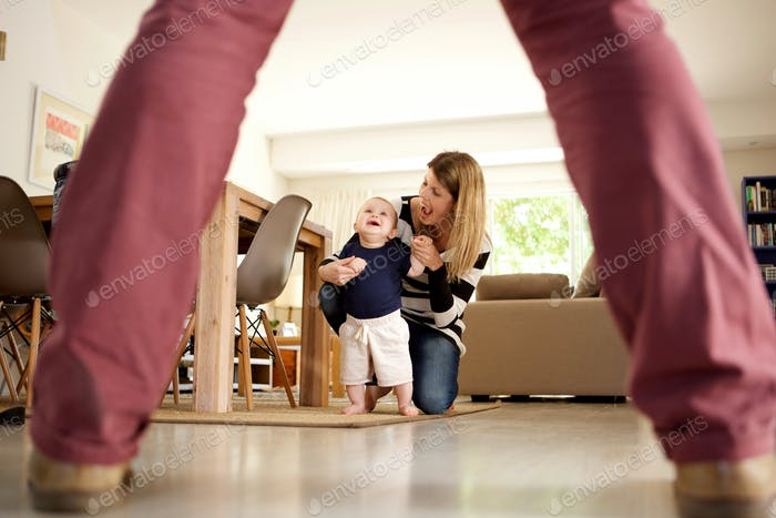 mother and child smiling together while learning to walk