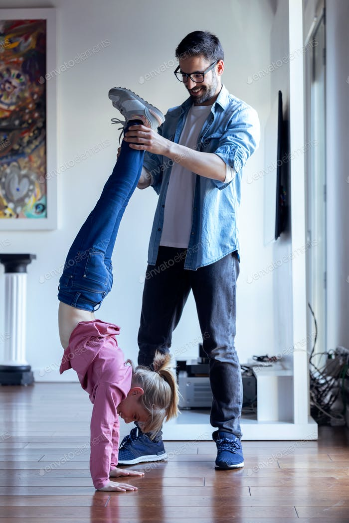 Handsome young father helping to pretty daughter to doing cartwheel at home.