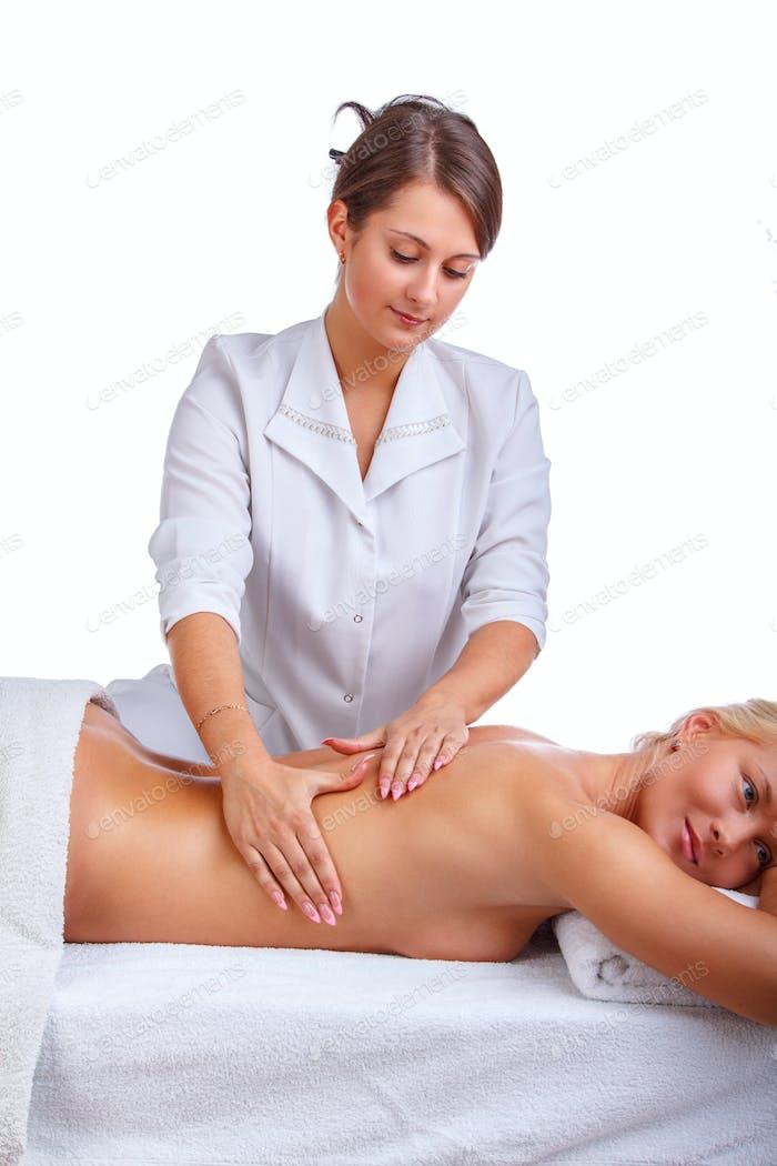 Женщина наслаждается расслабляющим массажем спины.