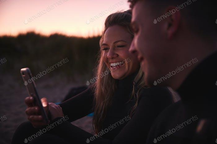 Paar tragen Neoprenanzüge sitzen am Strand mit Handy als Sonne hinter ihnen