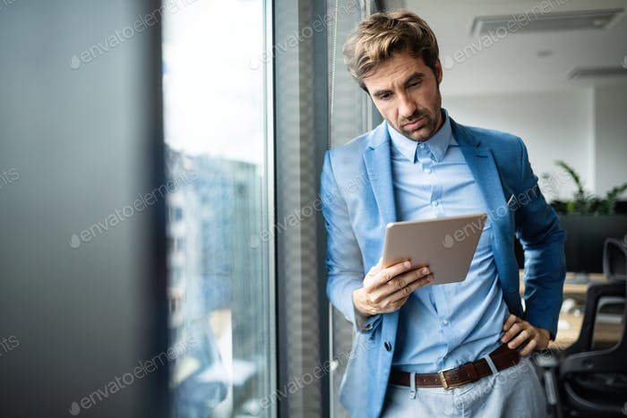 Portrait of confident young businessman using digital tablet
