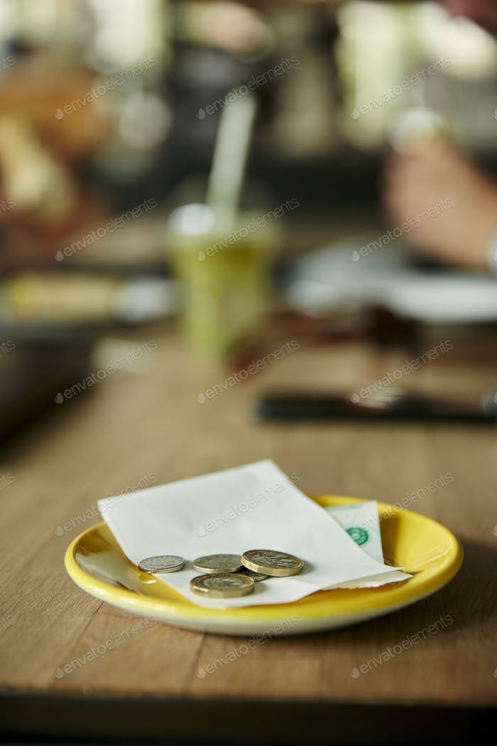 Coins and bill on restaurant table