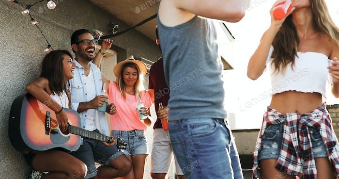 Freunde, die Spaß haben und Cocktails trinken im Freien auf einer Dachterrasse treffen sich zusammen