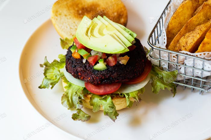 Vegan burgers with beetroot and beans served with fresh vegetables