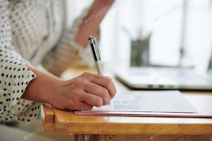Businesswoman correcting report