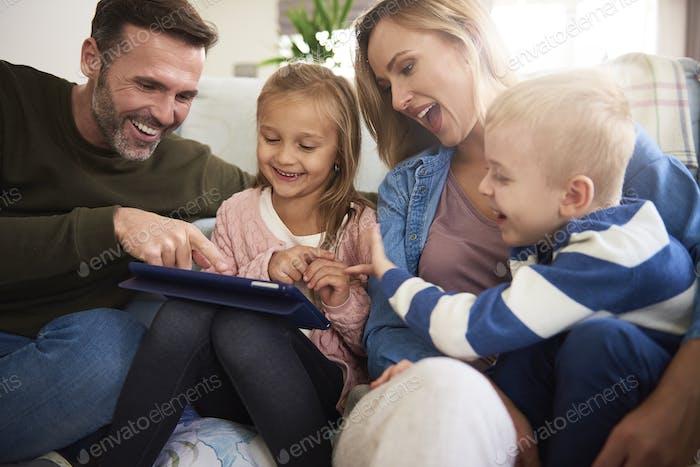 Familie mit Tablet verbringen Zeit zusammen im Wohnzimmer