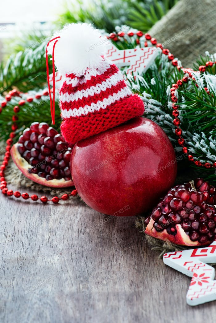 Red apple in hat and pomegranate with festive decorations