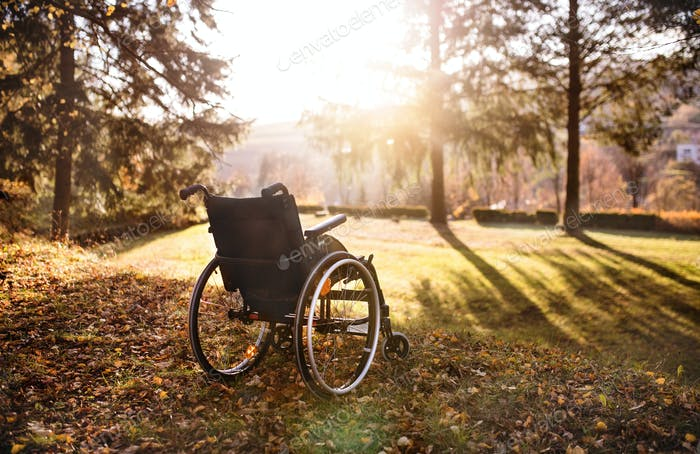 Empty wheelchair on a grass in park at sunset