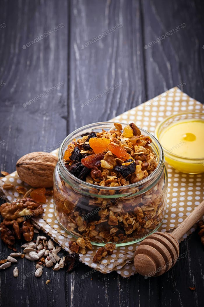 Granola in jar with nuts and dried fruit.