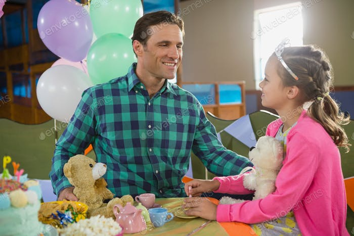 Father and girl interacting while playing toy kitchen set