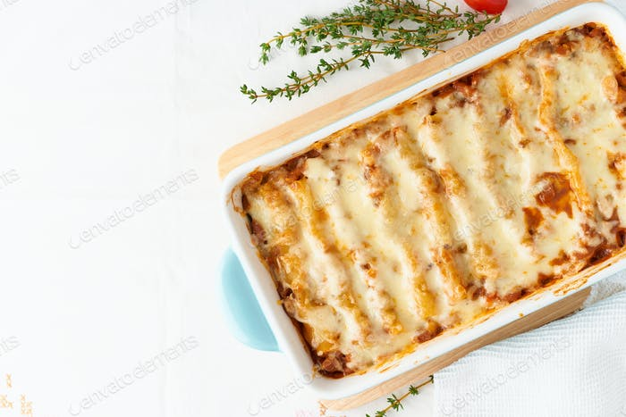 Cannelloni pasta with filling of ground beef, tomatoes, baked with bechamel