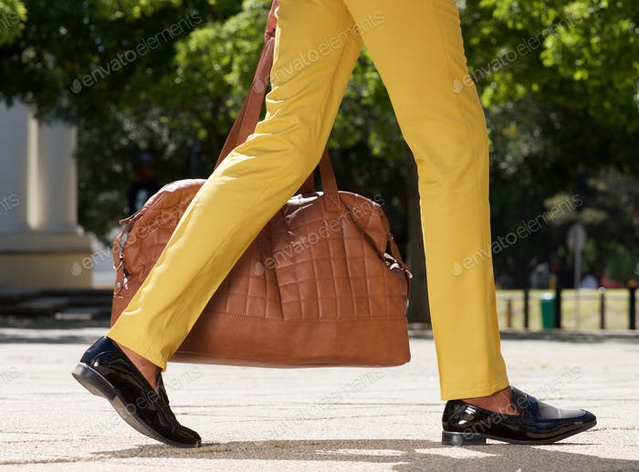 side view of man walking outdoors on city street with bag