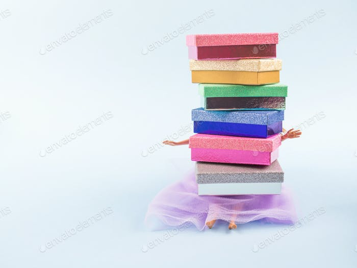 Doll in fashion dress under stack of gift boxes