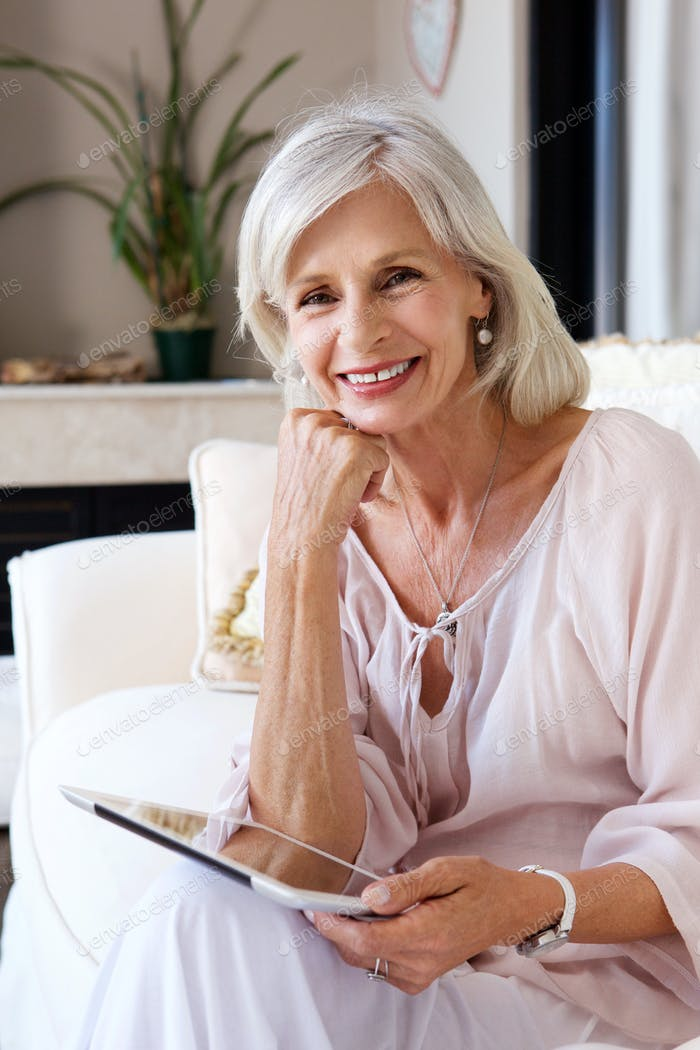 lächelnd ältere Frau im Wohnzimmer mit Tablet