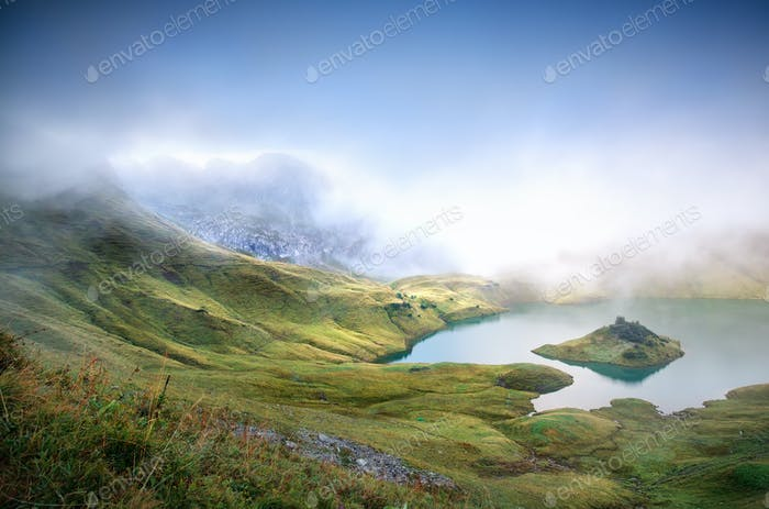 fog over alpine lake in mountains